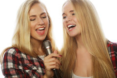 Two beauty girls with a microphone singing and having fun Stock Image