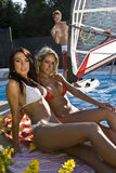 Two beauty and a guy. A brunette and a blonde beauty in bikini sitting by the pool and a buff guy on windsurfing board in a pool Stock Image