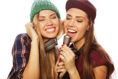 Two beauty hipster girls with a microphone singing and having f Royalty Free Stock Images