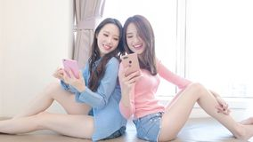 Two beauty woman on bed. Two beauty women use phone happily on the bed Royalty Free Stock Photography