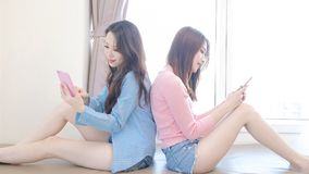 Two beauty woman on bed. Two beauty women use phone happily on the bed Stock Image