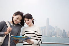 Two beauty woman look map i Royalty Free Stock Images