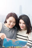 Two beauty woman look map Stock Images