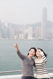 Two beauty woman look somewhere. Two beauty show something in hongkong Royalty Free Stock Image