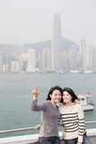 Two beauty woman look somewhere. Two beauty show something in hongkong Royalty Free Stock Photography