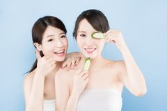 Two beauty woman. Two beauty women take cucumber with make up concept on the blue background Royalty Free Stock Photography