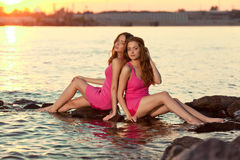 Two beauty women on the beach at sunset. Enjoy nature. Luxury gi Stock Photo