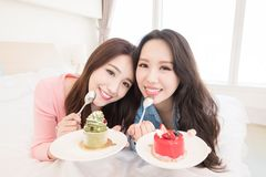 Two beauty woman eat cake. Two beauty women eat cake on the bed royalty free stock image