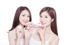 Two beauty women take brush. Two beauty skincare women take brush and dental floss on the white background stock photo