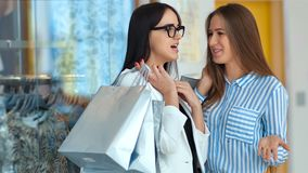 Two beauty young woman friends discussing something behind the storefront in a shopping mall.  stock footage