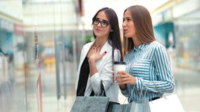 Two beauty young woman friends discussing something behind the storefront in a shopping mall.  stock video