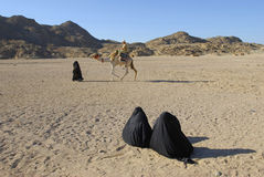 Two bedouin women watching camel ride Royalty Free Stock Photography