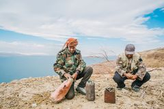 Two bedouins preparing a food and drink on top of the mountain in the valley of the Dead Sea stock photos