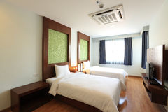 Two beds bedroom interior. Two beds with bedside table and lamp Stock Photos