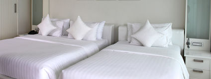 Two beds with white bedspreads and pillows Royalty Free Stock Image