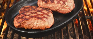 Two Beef Steaks On The Hot BBQ Flaming Grill Stock Photo