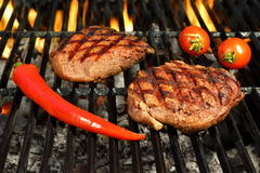 Two Beef Steaks On The Hot BBQ Flaming Grill Royalty Free Stock Image