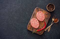 Two beefsteaks , peppers and old spoon, fork and cutting board o Stock Image