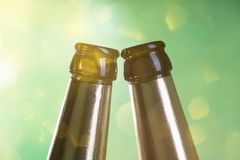 Two beer bottle necks. With green background stock photos
