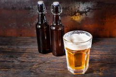 Two beer bottles near glass with a light beer and a head of foam. On old dark desk. Drink and beverages concept Royalty Free Stock Photo