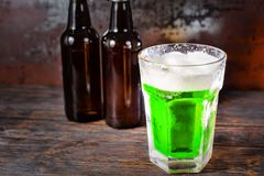 Two beer bottles next to glass with a green beer and a head of f. Oam on old dark desk. Drink and beverages concept Stock Photo