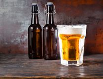 Two beer bottles next to glass with a light beer and a head of f. Oam on old dark desk. Drink and beverages concept Royalty Free Stock Image