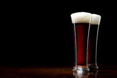 Two Beer into glass on a black and wooden table Royalty Free Stock Photography