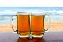 Two beer glasses on the beach. Two beer glasses on a wooden table, near the beach Royalty Free Stock Photography