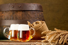 Two beer glasses with bundle of wheat. Still life of two beer glasses with bundle of wheat Royalty Free Stock Photos