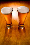 Two beer glasses on wet wood background Stock Photography