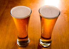 Two beer glasses on wood background Stock Photos