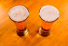 Two beer glasses on wooden table Stock Photography