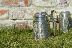 Two beer mugs on the grass near the brick wall Stock Photo