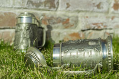 Two beer mugs on the grass near the brick wall Royalty Free Stock Photo