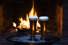 Two beers with fireplace on background. Two beers with flame in fireplace on background Royalty Free Stock Image