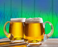 Two beers with hop field Royalty Free Stock Photography