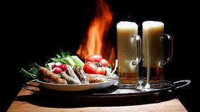 Two beers and sausages with flame on background stock video footage