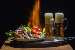 Two beers and sausages with flame on background. Two beers and sausages with campfire on background Royalty Free Stock Image