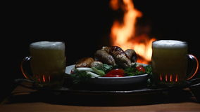 Two beers   and sausages with flame on background. Two beers with fireplace on background stock video footage