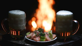 Two beers and shrimps with flame on background. Two beers and shrimps with campfire on background stock video footage