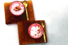 Two Beetroot super latte on marble background. Two Beetroot latte on white background. It is flower pastel on the top of the latter Stock Image