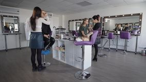 Two beginners make-up artists are trained to apply makeup professional cosmetics. As models have two girls, one blonde. Make-up rooms, where the training of stock footage