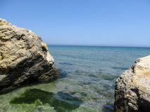 Two Beige-brown rocks are symmetrical around the edges of the photo, and between them the blue-turquoise sea. A clear sunny day and a clear sky without clouds Royalty Free Stock Images