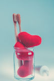Two beige dental brushes in glass cup with red hearts  on blue white background. Isolated. Toned photo. Love. Valentine day. Royalty Free Stock Photo