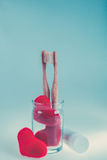 Two beige dental brushes in glass cup with red hearts  on blue white background. . Toned photo. Love. Valentine day. Royalty Free Stock Images