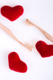 Two beige dental brushes with red hearts on white background. Isolated.  Love. Valentine day. Top view. Royalty Free Stock Image