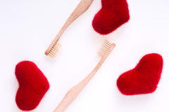 Two beige dental brushes with red hearts on white background. Isolated.  Love. Valentine day. Top view. Royalty Free Stock Photo