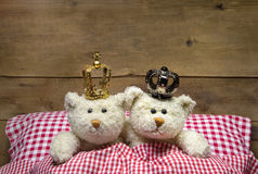 Two beige teddy bears lying in bed with crowns. Stock Photo