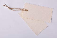Two beige textured paper tags tied with string stock photo