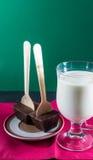 Two Belgian Chocolate Stirrers by mug of milk. Stock Image